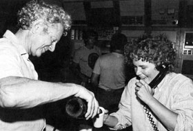 "Director Leon Lederman pours champagne for Linda Klamp as she ""spreads the news"" on Sunday, July 3"