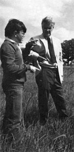 Robert Wilson, Director Emeritus and the original stimulus behind the Fermilab prairie restoration, watches Tony Donaldson (left), former Prairie Committee chairman gesticulate about the height of the prairie grasses in the Main Ring in June 1982