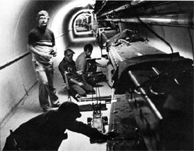 Merill Albertus (standing), Ken Meissner (foreground), Rine DeKing, and Gene Witt install a superconducting dipole magnet under a Main Ring magnet by gently sliding it into place