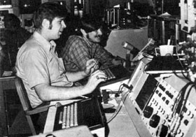 MONITORING THE BOOSTER BEAM: Alan J. Maier and Mark J. Kibilko (left to right) at the control panel during the first full week of Booster operation as it prepares to inject a beam into the Main Ring