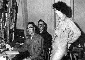 AT THE CONTROL PANEL: Ed Hubbard, Harlan Gerzevske, and Helen Edwards, all of Booster, (left to right) show their pleasure at the achievement of Booster's full design energy at 8 BeV.