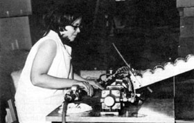 Linda Brunoehler operating the special automatic can opener developed for this unique operation by the NAL Machine Shop