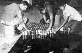 (Left to right) Harry McQuinn, Cliff Brown, and Phil Gerhardt set cans on an epoxy-coated panel