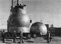 "The 15 foot bubble chamber arrives ""home"" after a temporary stop in The Village, following its arrival on October 25. Hemisphere on the ground is the upper portion of the vacuum tank which surrounds the chamber"