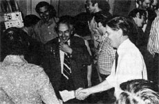 Dr. Wilson (R) shaking hands with fellow employees. Dr. Goldwasser (ctr.), Harry Howe, Safety Off.(plaid shirt)