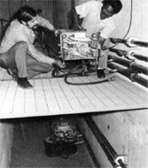 Don Richied and John Caffey inspecting a sweeping magnet in the M-3 line. The magnet in the pit is for the M-4 line, 4-feet below the ground level