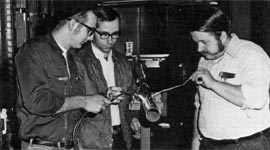 (L to R) Tony Rader, Richard Applegate and Jack Johnson preparing the nitrogen shield for the long liquid helium transfer line.