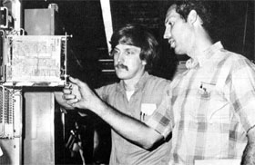 J. Walker (L) and L. Beverly checking circuit board in controls for magnet power supply in the Muon Area of NAL's Neutrino Section