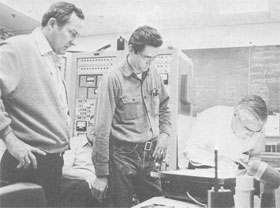 (L-R) R. Huson, G. Mulholland, and W. Fowler search film for tracks