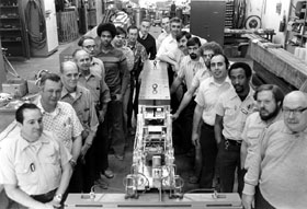 Proton Department staff with the special target drawer prepared for the Upsilon experiment. (L-R) Marty Solis, Billie Strickland, Del Hoffman, Bill Carter, Dave Eartly, Gary Smith, Mike Kleczewski, Jess Shaffer, Age Visser, John Gran, Ron Currier, Greg Gavin, Rick Bailey, Larry Alm, Carmen Rotolo, Glen Johnson, Bill Noe, Bill Thomas
